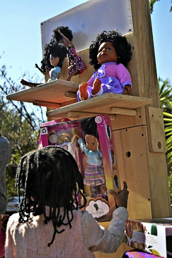 Books and black dolls are also on display at the market.