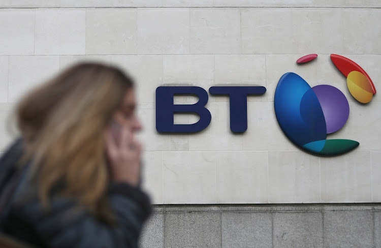 A woman talks on her phone as she passes the BT building in London, the UK. Picture: REUTERS/NEIL HALL