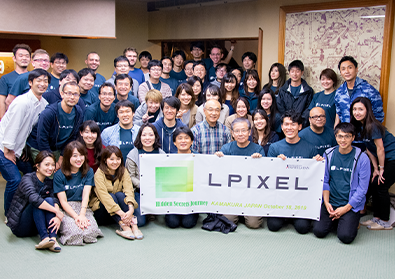 The team of LPixel surrounds a banner revealing their company's name.