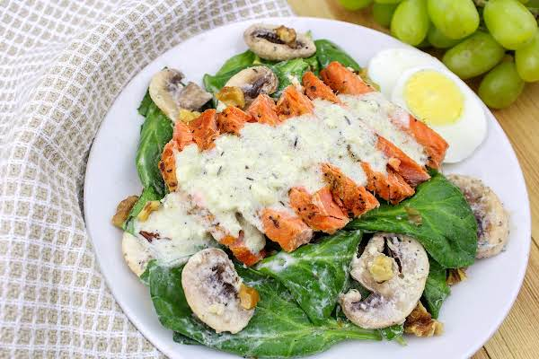 Plated Spinach Salad With Pan Seared Salmon.