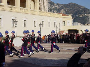 Photo: Which is the appearance of a military band from a building on the opposite side of the square.