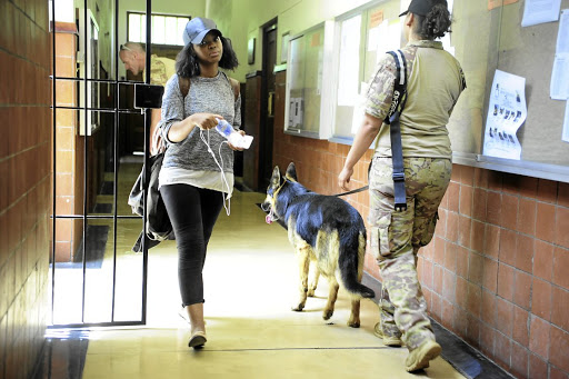 A student walks past a private security company guard and sniffer dogs checking for explosives in the corridors of Wits University. Safety of students needs to be a priority, the writer feels.