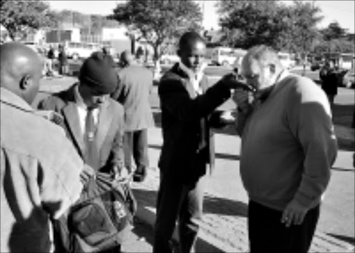 Check: Colin McDonald, principal of Northview High School, smells a pupil's hand. Concerned Balfour Park residents complained that pupils from schools in the area bunk classes and smoke in the streets. Pic. VATHISWA  RUSELO. 27/05/2009. © Sowetan.
