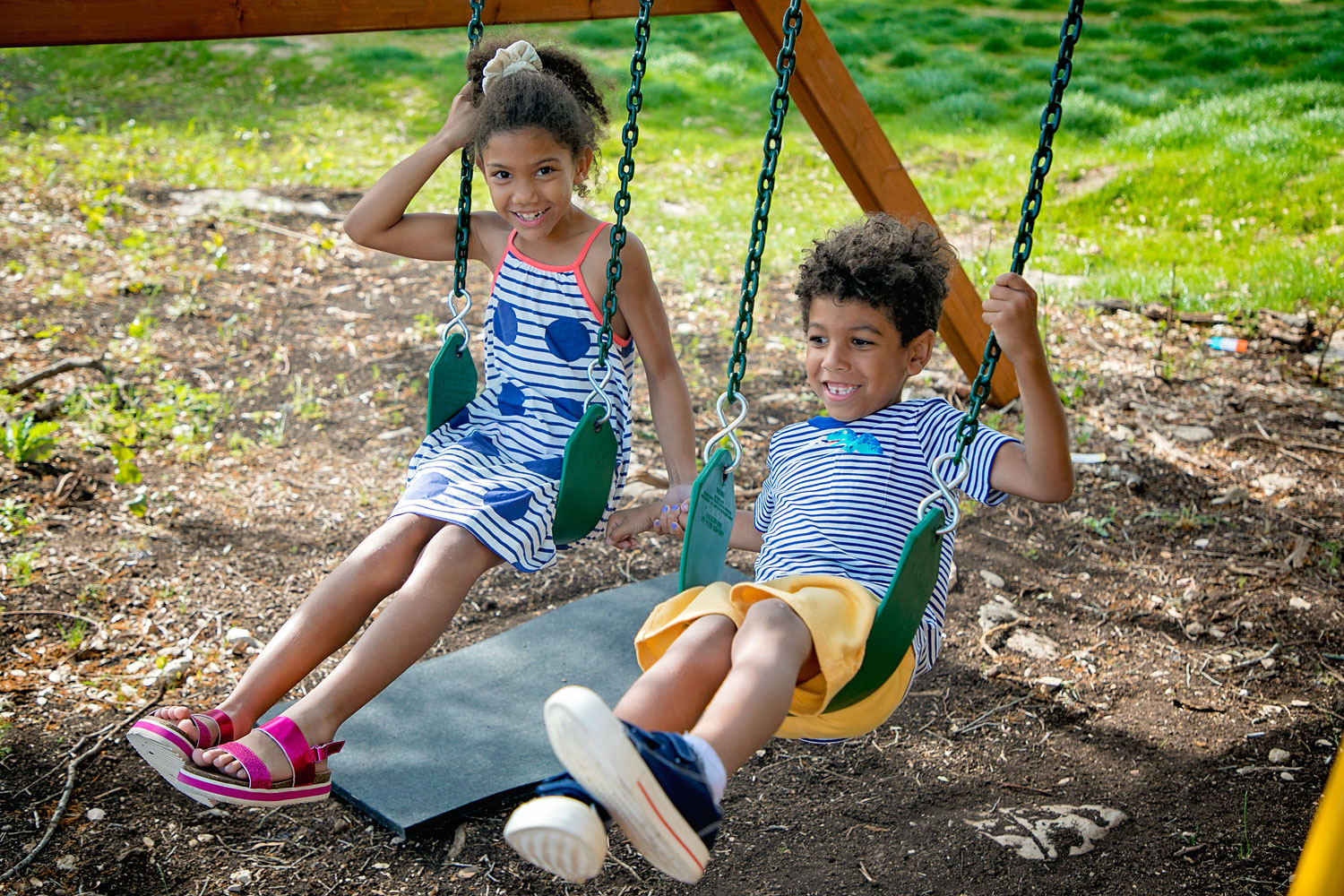 Biracial siblings holding hands on a swing wearing Stitch Fix kids clothes.