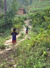 Photo: Familias transportando las láminas de metal para proteger las cabañas y tiendas de campaña de las lluvias del monzón