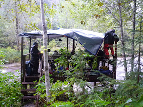 Photo: We're now on Gribbell Island, on a viewing stand, with a full day ahead to wait for a Spirit Bear to appear.  Luke is doing some quick work on the roof to keep us dry in the pouring rain.  Photo by Ben.