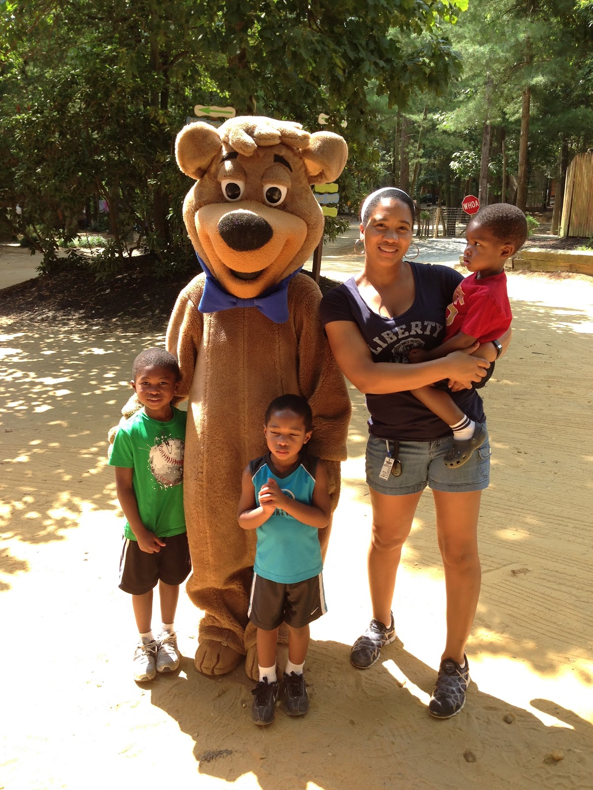 Mother and three young boys pose with Yogi Bear