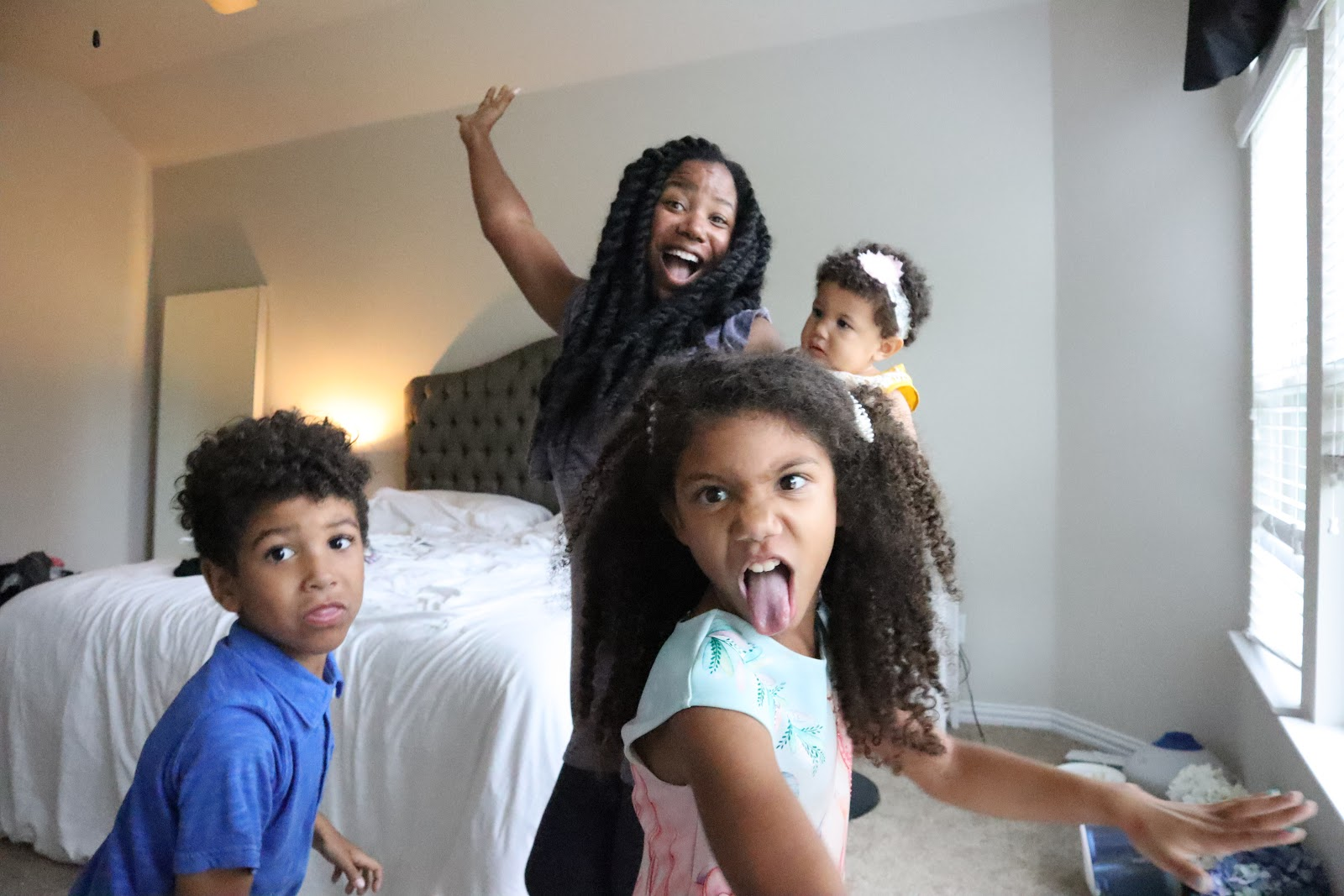 A mother posing with her three kids. Mother's Day questions to ask your kids each year.