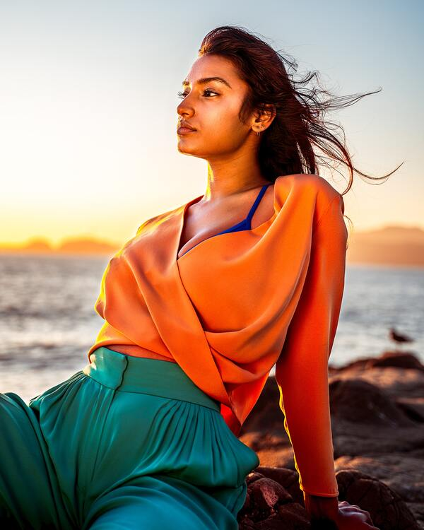 Foto de uma mulher sentada em umas pedras na praia com o por-do-sol ao fundo