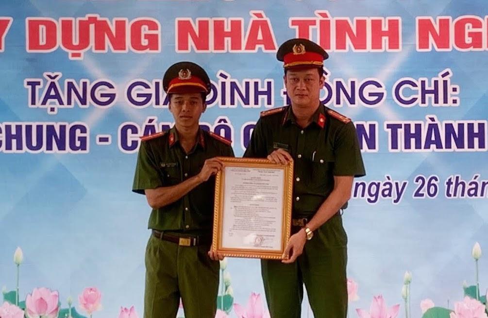 Đồng chí Thượng tá Trần Đức Cường, Trưởng Công an TP Vinh trao quyết định phê duyệt đầu tư xây dựng nhà cho đồng chí Thiếu uý Lưu Văn Chung.