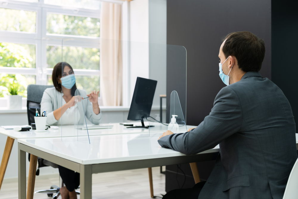 Homem de terno usando máscara de proteção e mulher atrás da divisória transparente