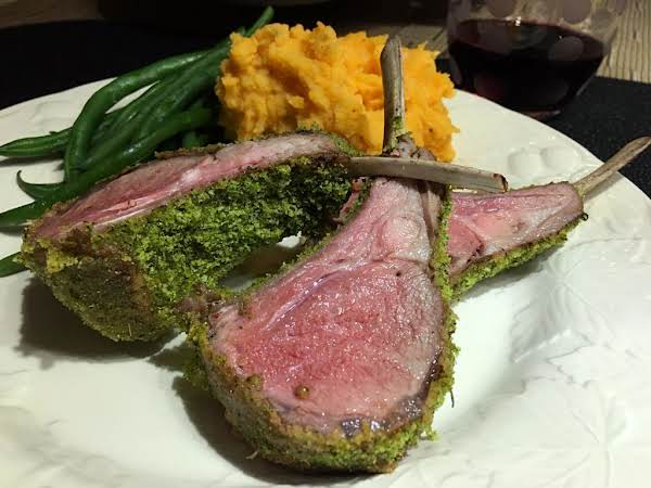 Three Crusted Lamb Chops On A White Plate With Mashed Potatoes And Green Beans.