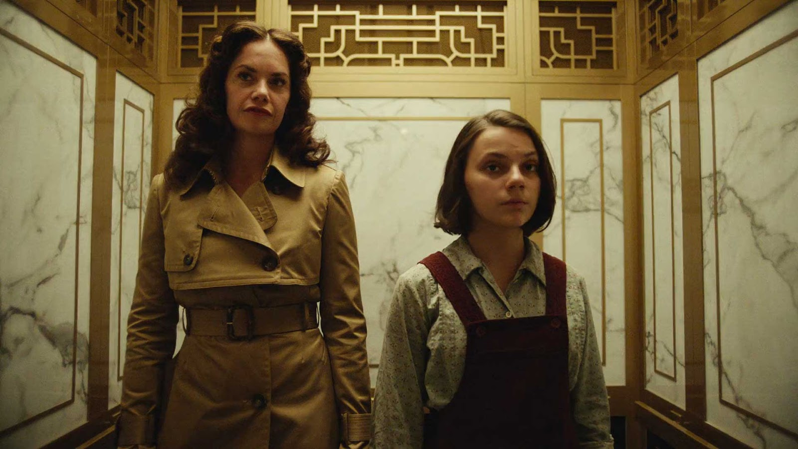 A young girl is standing next to an older woman in an ornate elevator.