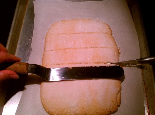 Slip the parchment paper with the shortbread onto a hard surface. Immediately sprinkle the...