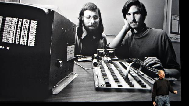 Steve Jobs in front of screen showing him with Steve Wozniak in the early days.