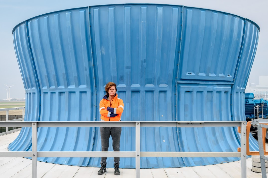 Woman stands in front of a large container