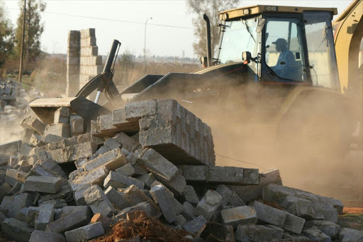 A catapillar at work during the structural demolition by the Department of Housing. File picture.