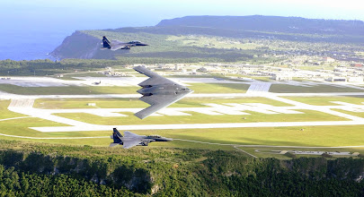 Photo: ANDERSEN AIR FORCE BASE, Guam -- F-15E Strike Eagles and a B-2 Spirit bomber fly in formation over the base.  The Strike Eagles are with the 391st Expeditionary Fighter Squadron from Mountain Home Air Force Base, Idaho.  The bomber is from the 325th Expeditionary Bomb Squadron from Whiteman AFB, Mo.  (U.S. Air Force photo by Tech. Cecilio Ricardo)