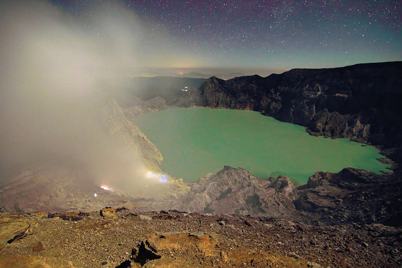 Photo: Crater rim of Ijen looking ito the crater.  To the left is a cloud of sulphuric acid rising from fumaroles erupting blue flame