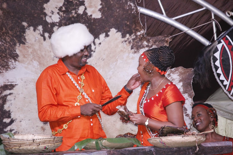 Lawyer Kamotho Waiganjo gives a piece of meat to his newly wedded wife and Kirinyaga govenor Anne Waiguru