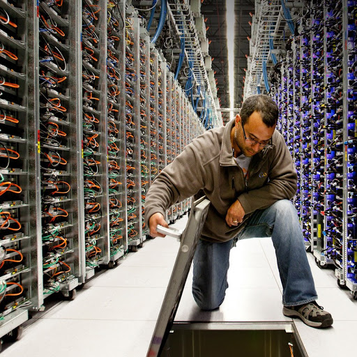 A male worker in a server room. looking down, lifting up a hatch in the floor