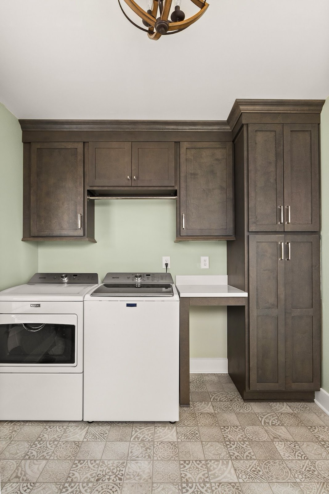 Superior construction and design Lebanon, TN 1970s Ranch Reno laundry room with dark cabinets ans small folding counter, patterned tiled floor