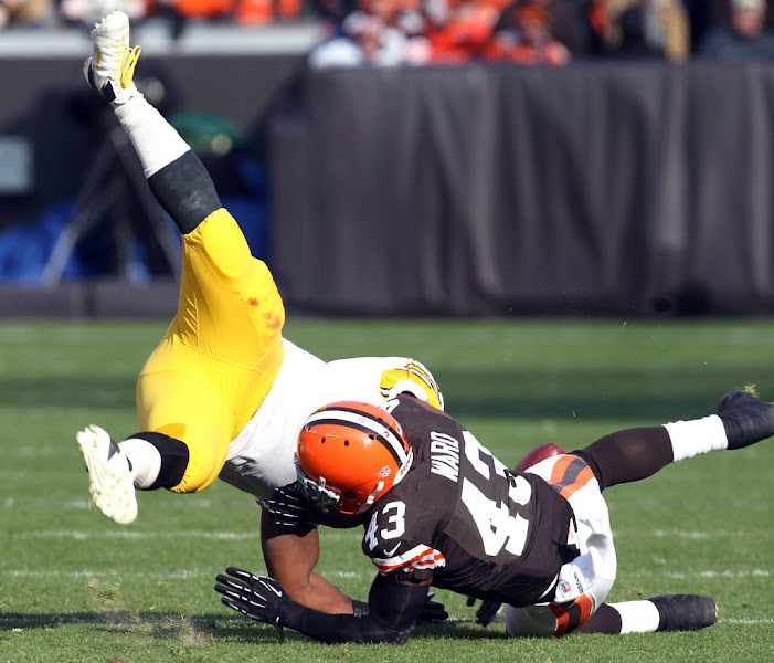 Photo: T.J. Ward upends Jonathan Dwyer, causing a fumble. (Chuck Crow, The Plain Dealer)