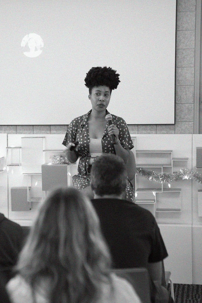 Women with microphone presenting to a room of people