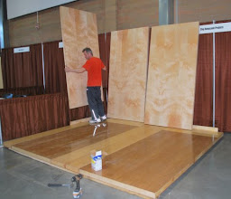 Photo: Adding the walls to a trade show booth. Sing Honeycomb wall panels are ready to fasten to the floor segments.