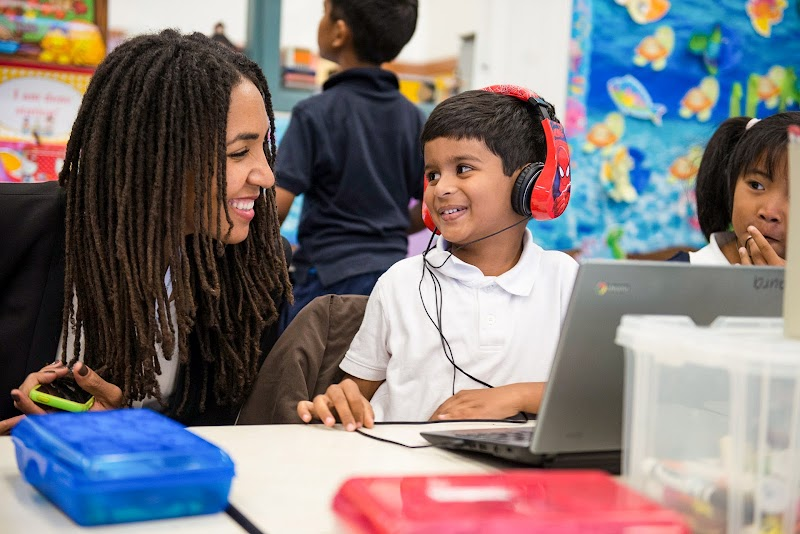 Child in red headphones and teacher with long hair in front of Chromebook computer in classroom.