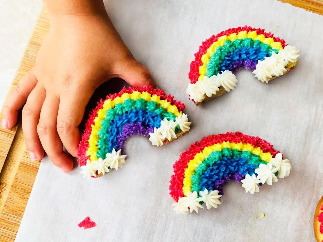 child holding gluten free rainbow donuts