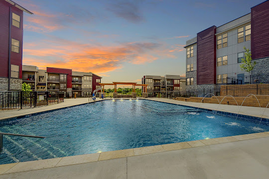 Residences at Echelon's resort-style pool at dusk with view of community apartment buildings