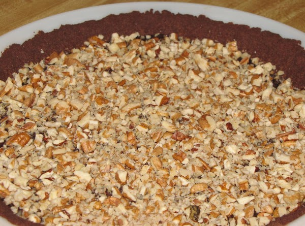 Spoon the hot ganache into the cooled crust, and sprinkle the nuts on top....