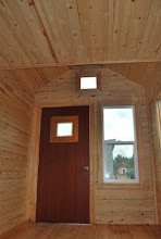 Photo: The inside of the front wall of a Tiny House with a honeycomb door, floor and walls.