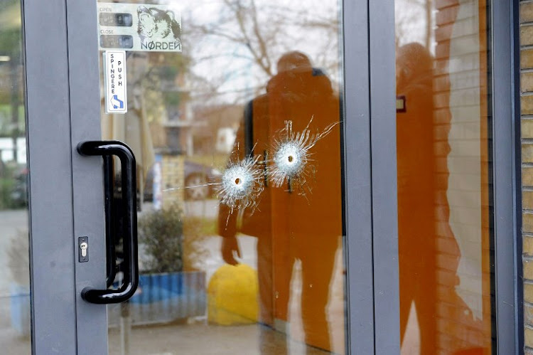 Bullet holes are seen in a glass door as police forensics officers carry out investigations in the area following the wounding of several foreign nationals in a drive-by shooting at Macerata, Italy on February 3, 2018.