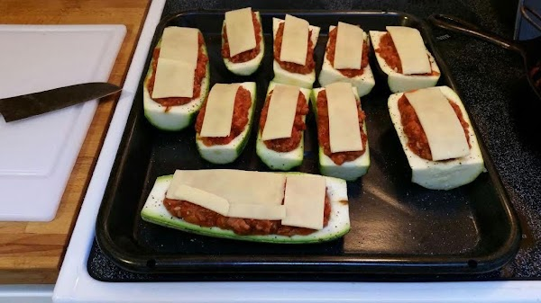 Pat zucchini shells dry with paper towels, then stuff with sausage mixture. Slice cheese...
