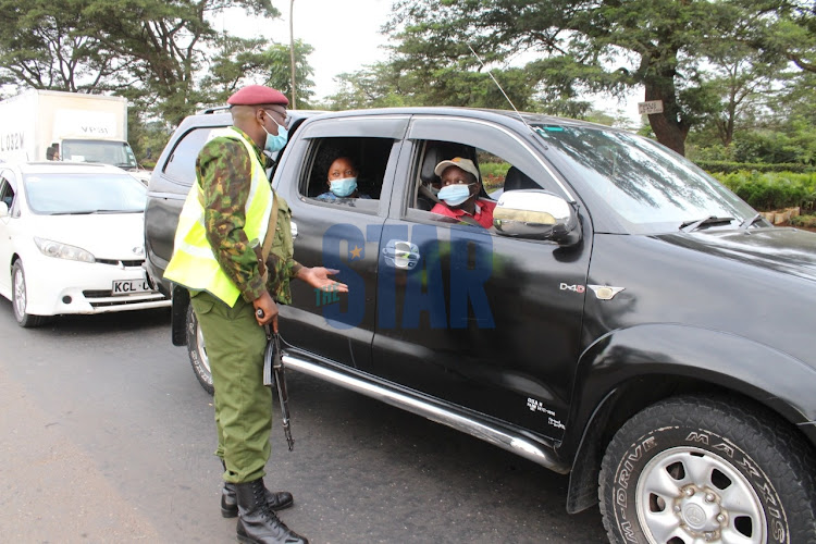 General Service Unit (GSU) officers monitor vehicles as they secure a checkpoint meant to indicate border of Kiambu and Murang'a counties in BluePost area, Thika on March 27, 2021