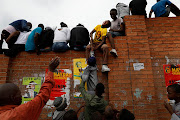 Residents of Alexandra try to find the best seats as ANC president Cyril Ramaphosa visits the Johannesburg township on April 11 2019.