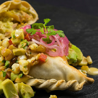 Green Chile Chicken Empanadas with Corn Avocado Relish & Pickled Onions.
