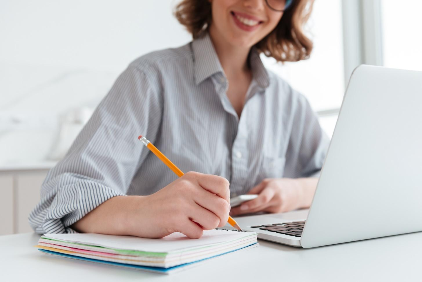 young-smiling-woman-striped-shirt-taking-notes-while-sitting-table-light-apartment