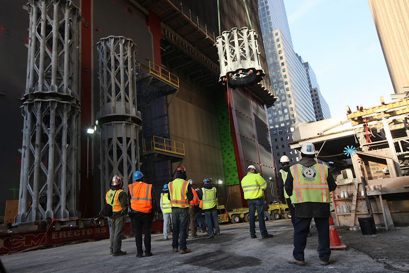Photo: NEW YORK, NY - DECEMBER 12:  Workers  watch as the first piece of the spire is hoisted atop One World Trade Center on December 12, 2012 in New York City.  The first of 18 sections of spire was hoisted atop the 104-story building by crane this morning.  (Photo by Mario Tama/Getty Images)