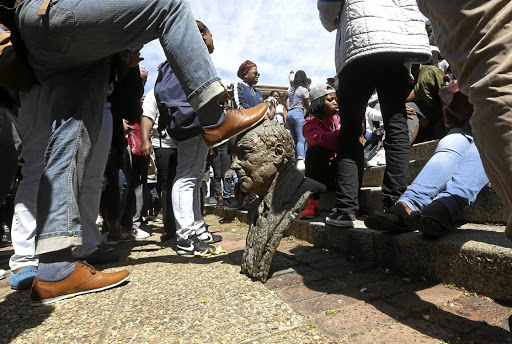 Wreaking destruction: University of Cape Town students vandalise a statue during a Fees Must Fall protest, which centred on free higher education. Laboratories, libraries and buildings were set alight and vandalised on campuses across the country during the protests. Picture: ESA ALEXANDER/ THE TIMES