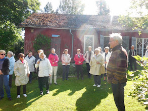 Photo: Loviisan Kuninkaanlammen isäntä kertomassa kotipaikastaan. Taustalla kahvilana ja myyntitilana toimiva vanha varastorakennus.