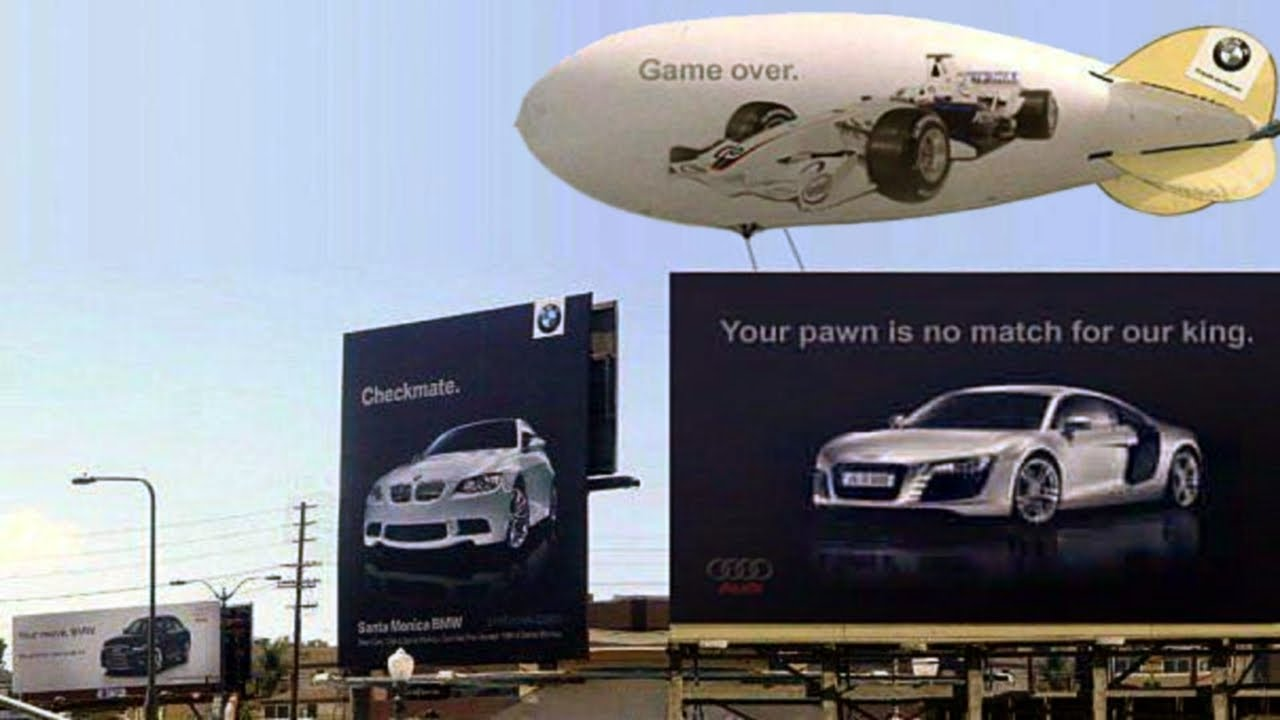 2 giant billboards about automobile next to each other, with a blimp on top