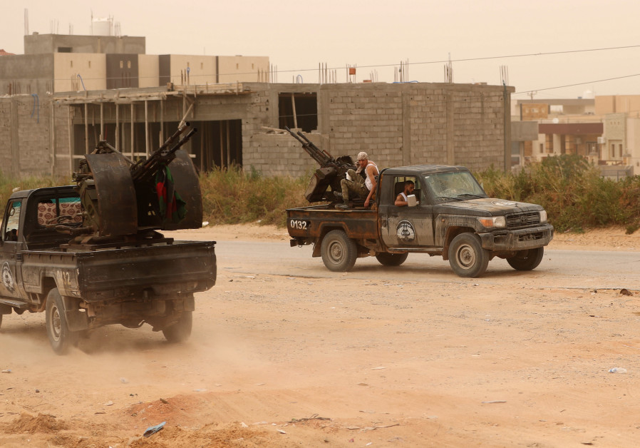 LIBYAN GOVERNMENT forces take position during fighting in Ain Zara, in Tripoli, earlier this week