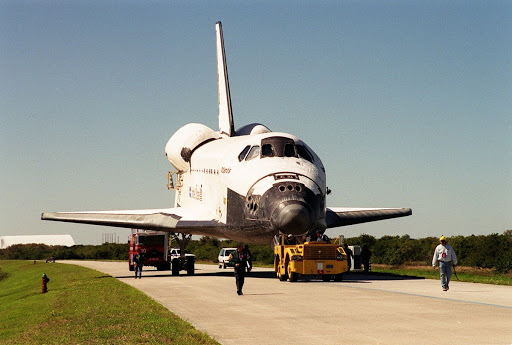 Atlantis moves along the tow-way from the KSC Shuttle Landing Facility to the Orbiter Processing Facility.