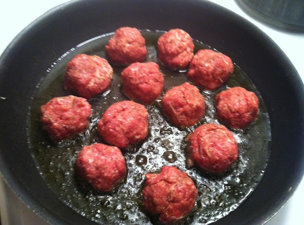In a large frying pan add 1/4 inch of olive oil and place meatballs...