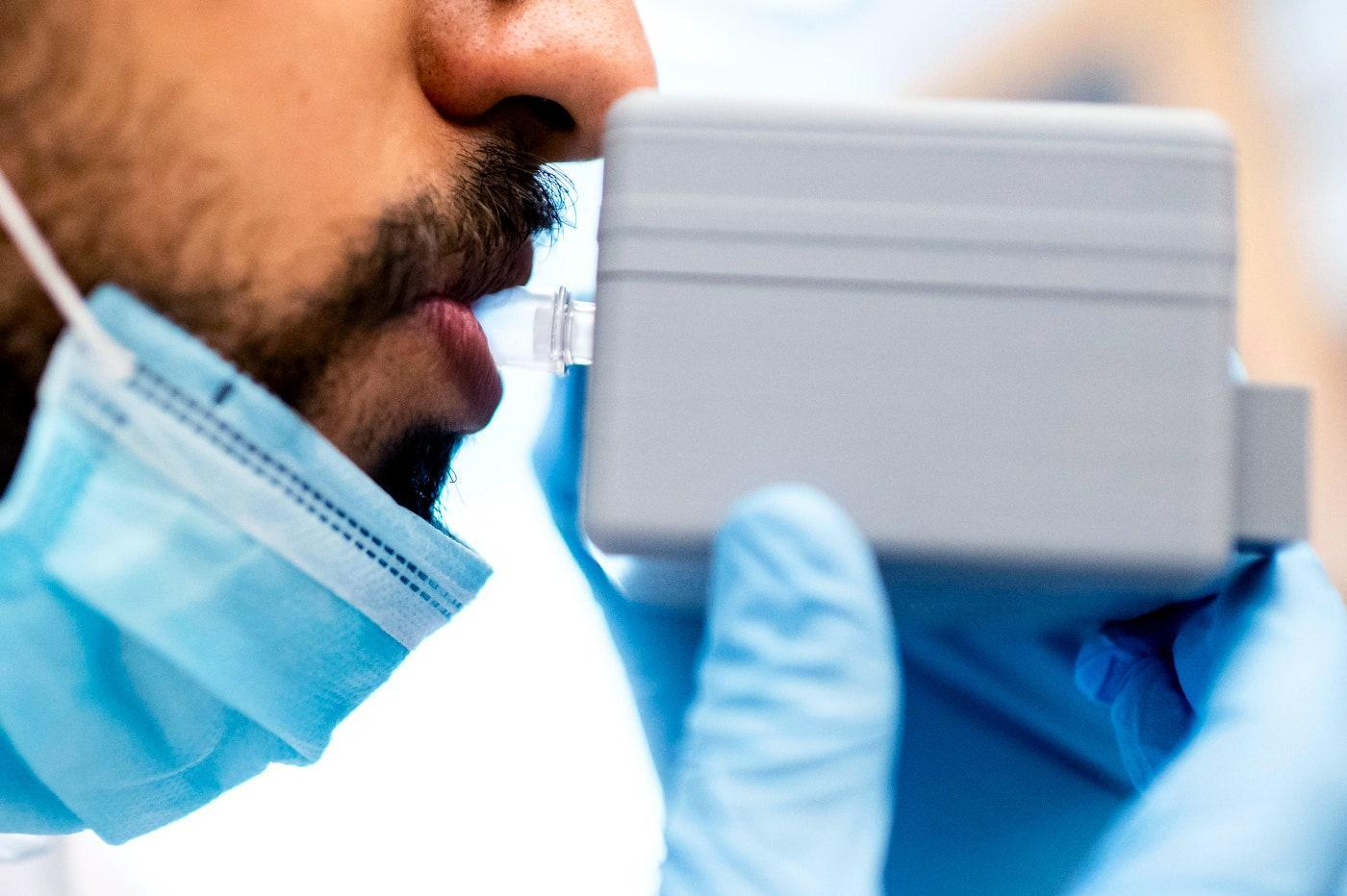 man breathing into breathalyzer