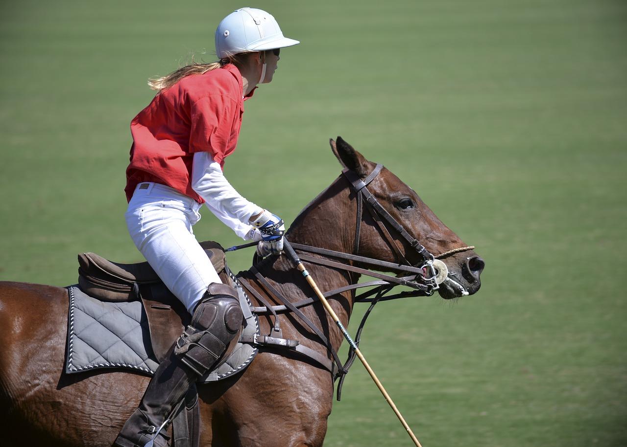 woman riding a horse during a polo match,