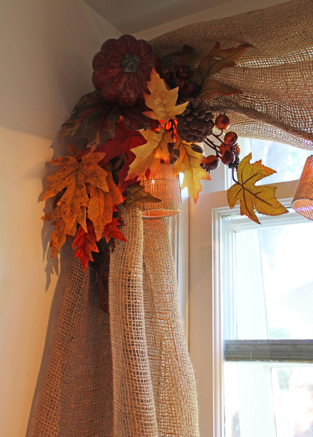 fall window curtains held with fall leaves, pine cones and pumpkins